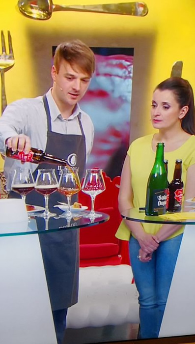 "Nico De Backer serving as beer sommelier on RSI's ""Cuocchi d'artificio"" cooking show, next to Francesca Margiotta"